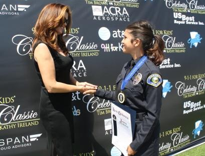 Kathy Ireland congratulates an Anaheim Police Dispatcher on her award.